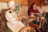 MUSKOGEE, OK - MAY 24: Ladies make yarn on spinning wheels at the Oklahoma 19th annual Renaissance Festival on May 24, 2014 at the Castle of Muskogee in Muskogee, OK