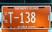 ARUBA - CIRCA DECEMBER 2013 - Colorful bright orange tourist number plate from Aruba with the words - One Happy Island - and the internet address with the number T-138 circa December 2013
