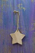 Hanging Handmade Wooden Star On Wooden Purple Background For Christmas