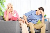 Sad woman arguing with her husband seated on sofa at home