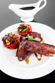 fresh red beef meat steak barbecue garnished vegetable salad and basil on white plate over black woo