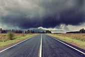 asphalt road and dark thunder clouds over it .