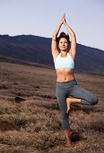 Attractive woman practicing yoga outdoors at sunset