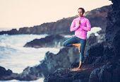 Woman practicing yoga at seashore