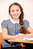 Smiling schoolgirl sits at a desk during a lesson. Education.