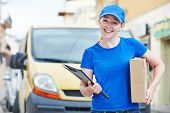 Smiling female postal delivery courier woman outdoors  in front of cargo van delivering package