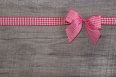 Top View Of A Red Checked Ribbon Decoration On Wooden Background