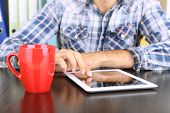 Man sitting on wooden table and working on tablet closeup