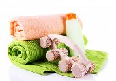 Wooden roller brush, towels and shampoo on white background isolated