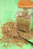 Bay seeds in a glass square bottle with wooden lid on green background