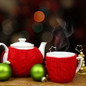 Christmas decoration, teapot and cup in front of sparkle lights
