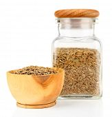 Square glass bottle and wooden round bowl with seasoning on white background isolated