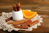 White round cup with seasoning and a piece of orange on a white lace napkin on brown wooden backgrou