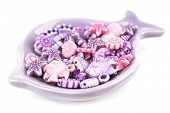 Beads for children in ceramic dish isolated on white