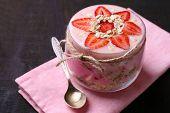 Healthy breakfast - yogurt with  strawberries and muesli served in glass jar, on wooden background