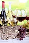 Bottles and glasses of wine and ripe grapes on table on natural background