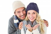 Attractive couple in winter fashion smiling at camera on white background