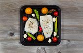 stock photo of peppercorns  - Top view of fresh raw Cod Fish Fillets in cooking pan with tomatoes garlic peppers and peppercorn salt on rustic wooden boards - JPG