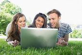 Happy students using laptop outside at the university