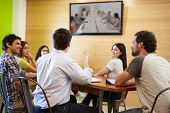 Designers Sitting Around Table In Meeting Looking At Screen