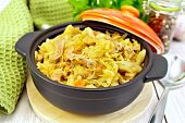 Cabbage stew with meat in black brazier on light board