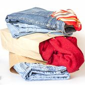 Shopping: a woolen jumper and jeans of various shades in paper packages