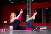 Two Smiling Girls Do Stretching Exercises On Mats In Fitness Center