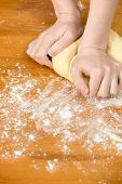 Woman's Hands Knead Dough On The Table