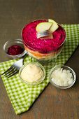 Russian herring salad in glass bowl on wooden table background