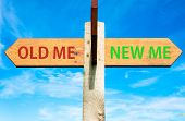 image of change management  - Wooden signpost with two opposite arrows over clear blue sky Old Me and New Me Life change conceptual image - JPG