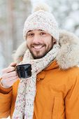 season, christmas, drinks and people concept - happy smiling young man with cup drinking hot tea in winter forest