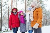 love, relationship, season, friendship and people concept - group of smiling men and women talking in winter forest
