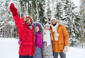 love, relationship, season, friendship and people concept - group of smiling men and women pointing finger in winter forest