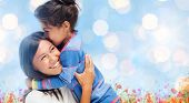 people, happiness, love, family and motherhood concept - happy mother and daughter hugging over blue lights and poppy field background