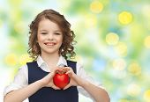 love, charity, holidays, children and people concept - smiling little school girl with red heart over green lights background