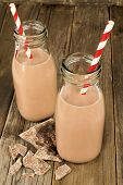 Chocolate milk in bottles on wood