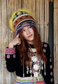 stock photo of hmong  - Traditionally dressed Mhong hill tribe woman thinking in the wooden cottage - JPG