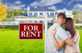 For Rent Real Estate Sign and Affectionate Military Couple Looking at Nice New House.