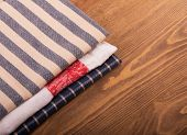 Old linen kitchen towels folded on dark wooden table