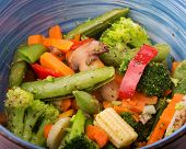 foto of steam  - Closeup of healthy steamed vegetables in a blue bowl - JPG