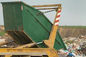 picture of junk-yard  - Truck tipping garbage from container on junk yard - JPG