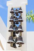 image of blue-bell  - Many bells on a white plaster tower under a clear blue sky - JPG