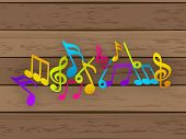 Colorful music notes on wooden background.