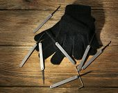 Lock picks with gloves on wooden table
