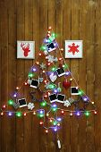 Garland in shape of Christmas tree on wooden wall background
