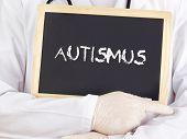 Doctor Shows Information On Blackboard: Autism In German