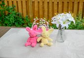 stock photo of easter lily  - A plush pink and yellow Easter bunny sit in front of a basket with a glass vase of Easter lilies beside them on a table in a garden setting outside during the spring season - JPG