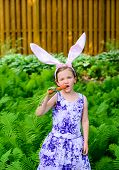 Young Girl In Bunny Ears Eating A Carrot