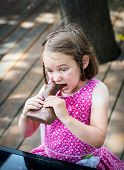 Little Girl Biting Into A Chocolate Bunny