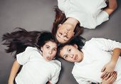 Three teenage sisters lying on the floor